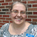 Library director Kate Kosior smiling with brick background