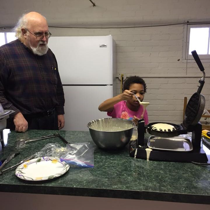 Library patron supervising child patrol cooking waffles